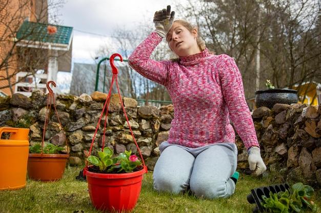 La femme est fatiguée de planter des plantes dans des pots