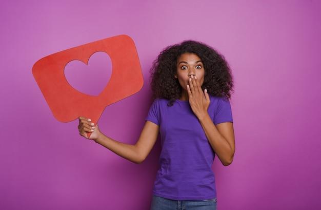 La femme est heureuse parce qu'elle reçoit des coeurs sur une application de réseau social.