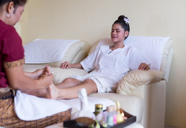 Une femme est heureuse de profiter d'un massage des pieds avec la greflexologie dans un spa bien-être