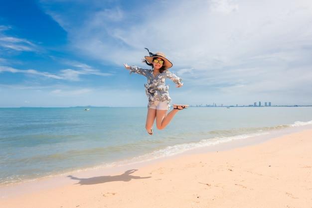 La femme est heureuse et saute pendant ses vacances.
