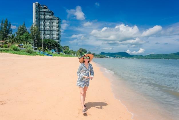 La femme est heureuse et se promène sur des vacances à la plage.