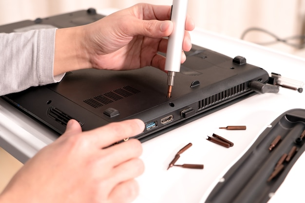 Une femme est un ordinateur portable de réparation utilisant un tournevis, la réparation et l'entretien