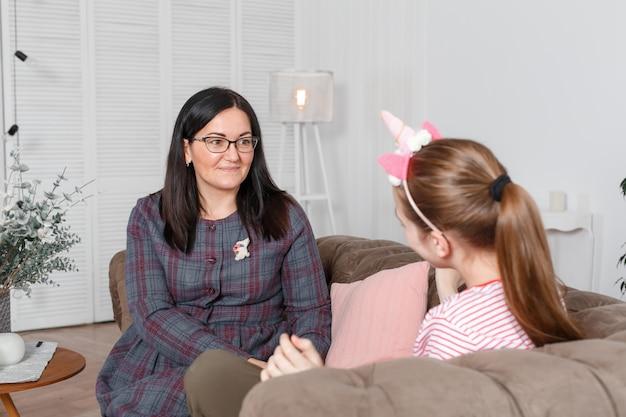 Une femme est un psychologue pour enfants professionnel parlant à une adolescente dans son bureau confortable