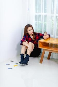 La femme est sérieuse et est assise dans le coin de la pièce. concept clair
