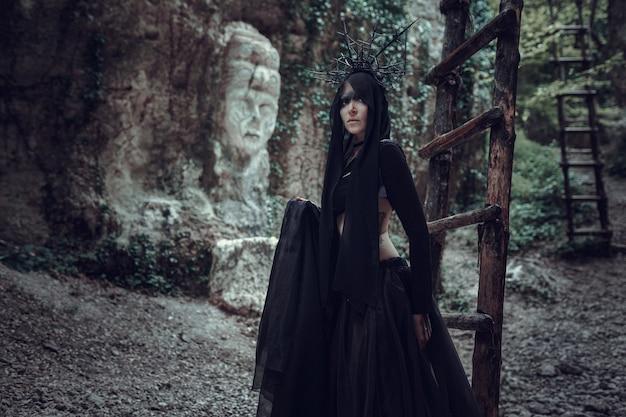 Une femme est un sorcier prophète et un prédicateur dans un manteau mystique noir avec une capuche