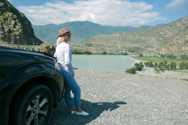 Une femme est sortie de la voiture et regarde les montagnes