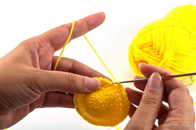 Femme est en train de crocheter sur fond blanc