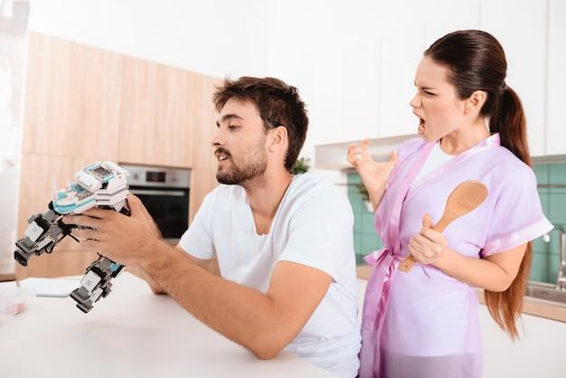 La femme est vêtue d'une robe rose et crie après l'homme.