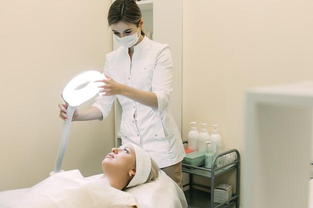 Femme esthéticienne ajuste la lampe au-dessus du patient