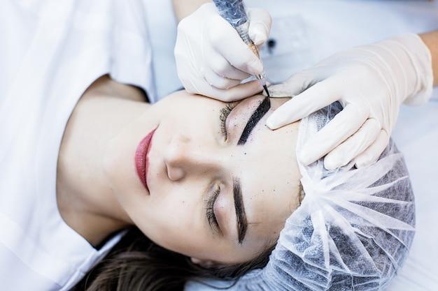 La femme esthéticienne applique le maquillage permanent sur les sourcils de tatouage de sourcils sur de beaux modèles dans un salon de beauté