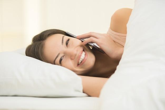 La femme était allongée sur le lit et au téléphone