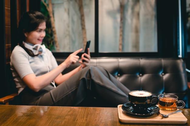 Une femme était assise dans un café avec des écouteurs jouant sur le téléphone et un masque médical pour protéger covid-19.