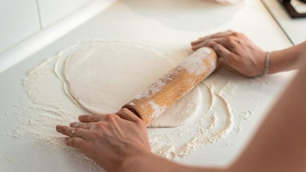 Femme étalant la pâte à pizza
