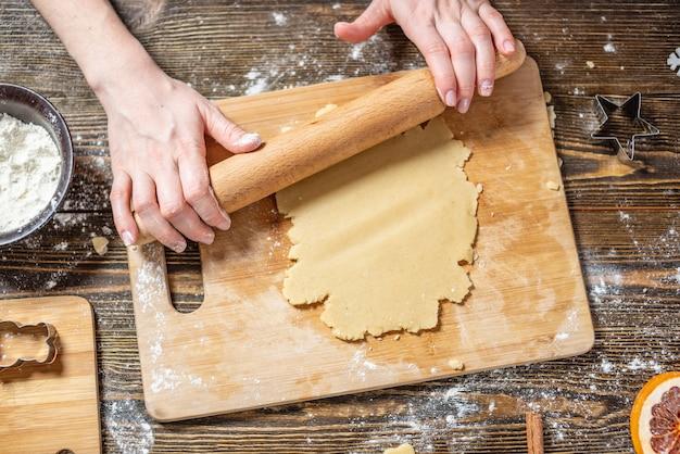 Femme étale la pâte avec un rouleau à pâtisserie et des formes