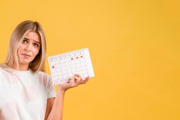 Femme étant contrariée et tenant le calendrier de la période