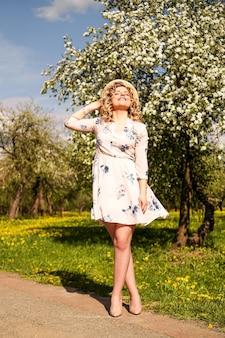 Femme d'été souriante avec chapeau de paille dans le parc - jardin de pommes au printemps journée ensoleillée