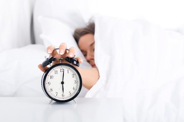 Femme éteignant le réveil