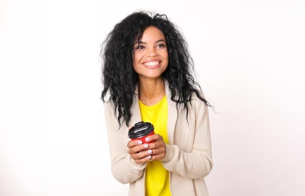 Une femme ethnique africaine heureuse en cardigan beige et t-shirt jaune tient une tasse de café en papier rouge et sourit en regardant vers la droite