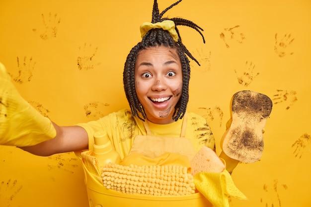 Une femme ethnique heureuse fait le ménage et le nettoyage rend le selfie tient une éponge sale porte des gants en caoutchouc sourit largement fait du linge sale à l'intérieur contre un mur jaune