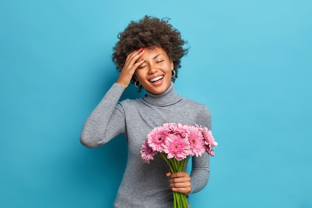 Femme ethnique à la peau sombre optimiste insouciante tient le bouquet de belles fleurs sourit largement