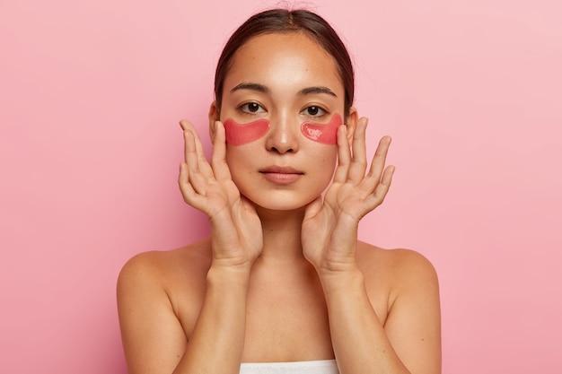 Femme ethnique sérieuse avec des patchs de collagène sous les yeux, fait un masque de beauté, veut paraître jeune et fraîche, a des procédures de cosmétologie après le bain, regarde droit, montre les épaules nues