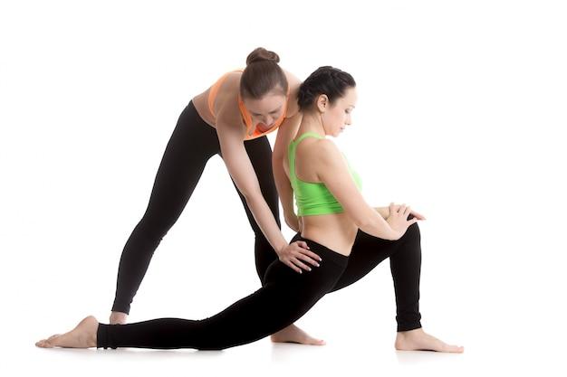 Femme étirant sa jambe avec une autre femme
