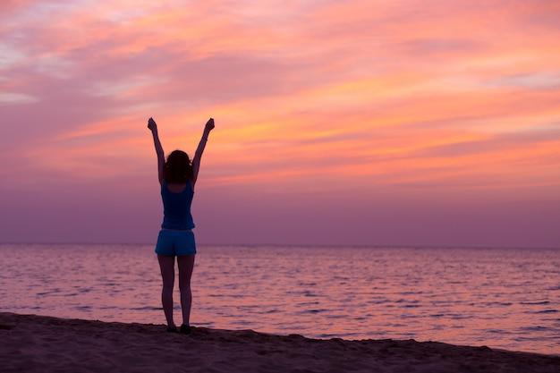 Femme étirant ses bras au crépuscule
