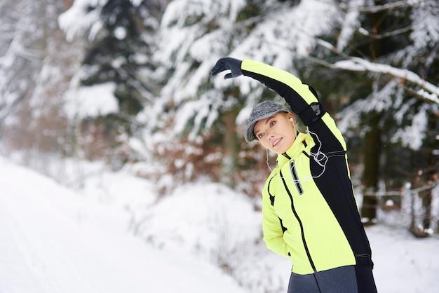 Femme étirant ses bras et ses mains dans la forêt d'hiver