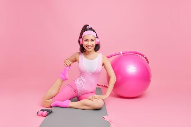La femme étire les jambes montre sa flexibilité étant de bonne humeur porte des écouteurs sur les oreilles vêtements de sport listebns musique tout en faisant des exercices de gymnastique pose sur karemat sur mur rose