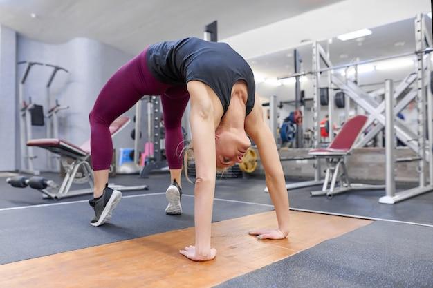 Femme, étirement, corps, tout, faire, yoga, gymnase