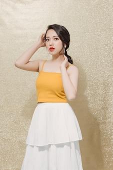 Femme étonnante posant sur le mur brillant d'or.