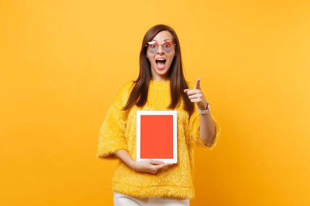 Femme étonnée dans des lunettes de coeur pointant l'index sur l'appareil photo, tenant un ordinateur tablette avec un écran vide noir vierge isolé sur fond jaune vif. concept de mode de vie des émotions sincères des gens.