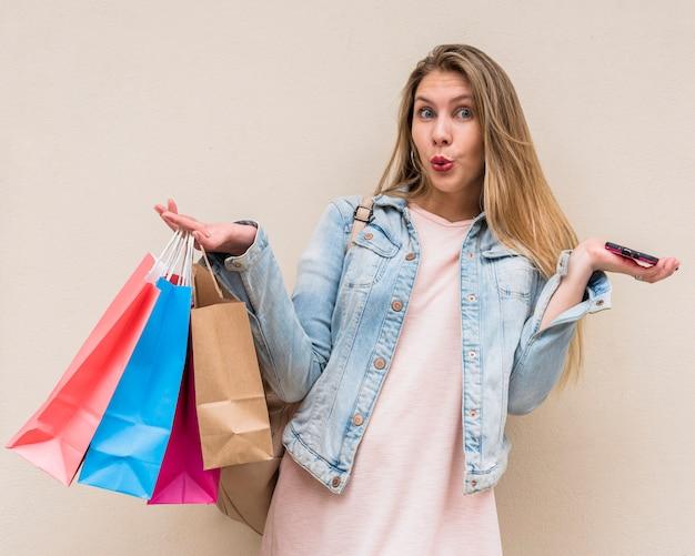 Femme étonnée debout avec des sacs à provisions et smartphone