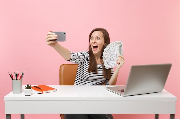 Femme étonnée faisant une prise de vue en selfie sur un téléphone portable tenant un paquet de dollars en espèces tout en travaillant au bureau avec un ordinateur portable