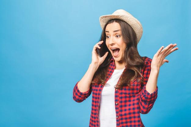 Femme étonnée gardant la bouche grande ouverte à la surprise de parler sur téléphone mobile