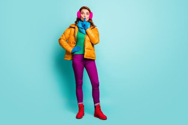 Femme étonnée ne pas partager des informations privées mettre l'index bouche porter des bottes jaunes pantalon violet pantalon cavalier vert.