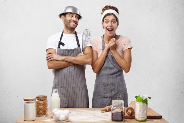 Une femme étonnée et ravie en tablier regarde avec des yeux écarquillés et de l'excitation se rend compte qu'elle a préparé un très délicieux dîner avec l'aide de son mari