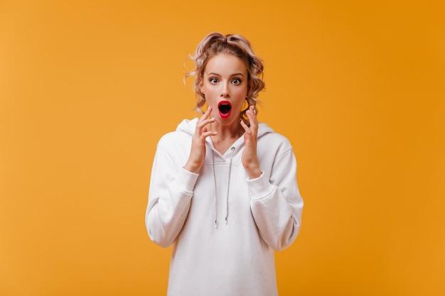 Une femme étonnée en sweat à capuche blanc comme neige fait un visage choqué