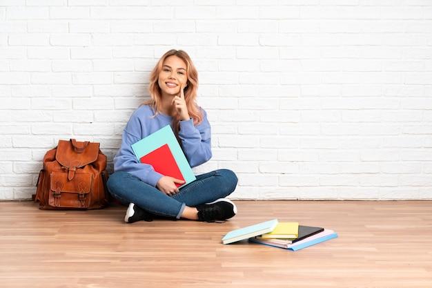Femme étudiante adolescente aux cheveux roses assis sur le sol à l'intérieur souriant avec une expression heureuse et agréable
