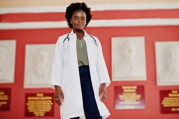 Femme étudiante afro-américaine en blouse de laboratoire avec stéthoscope à l'intérieur de l'université médicale.