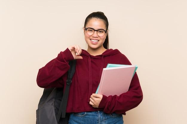 Femme étudiante asiatique jeune étudiante sur mur isolé fier et satisfait