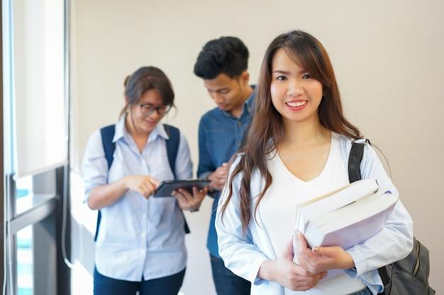Femme étudiante asiatique souriant et porter des manuels avec un groupe d'amis à l'université intérieure