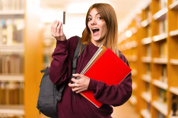 Femme étudiante détenant une carte de crédit sur un arrière-plan flou. retour à l'école