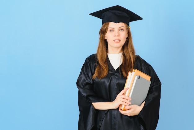 Femme étudiante diplômée portant chapeau et robe de graduation, sur fond bleu