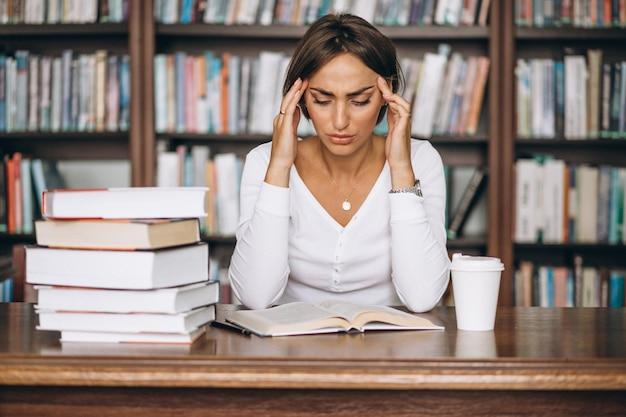 Femme étudiante étudiant à la bibliothèque et buvant du café