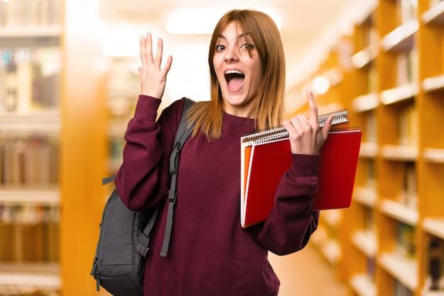 Femme étudiante faisant un geste de surprise sur un arrière-plan flou. retour à l'école
