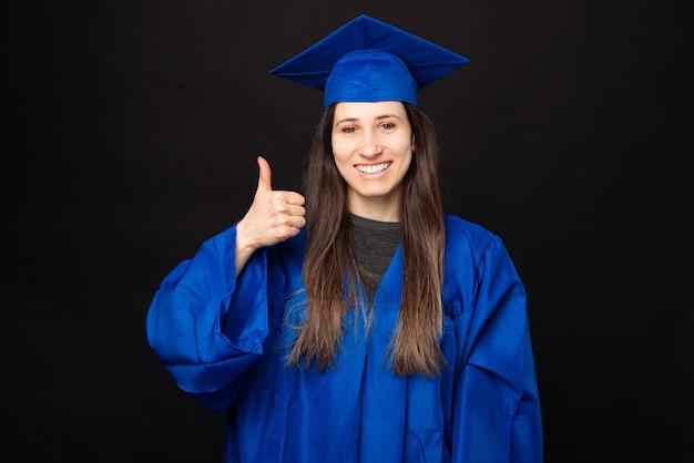 Femme étudiante gaie en baccalauréat diplômé et montrant le pouce vers le haut