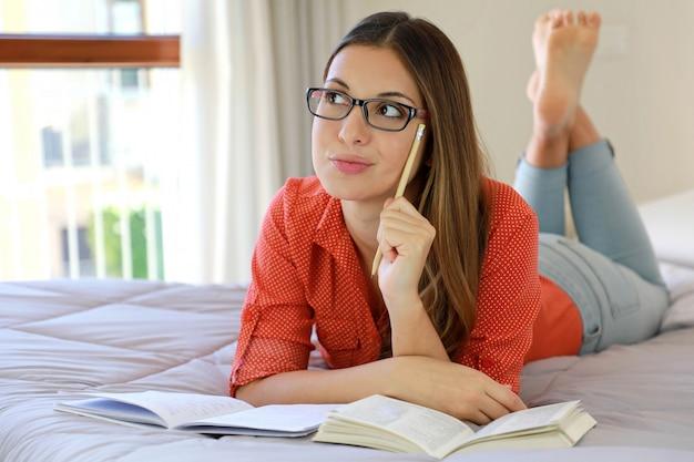 Femme étudiante jeune réfléchie étudiant confortable à la maison look