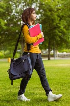 Femme étudiante avec des livres dans le parc