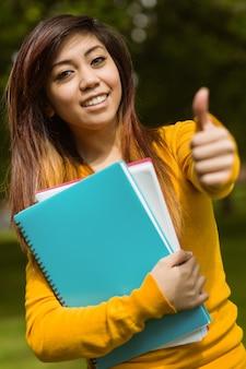 Femme étudiante avec des livres gesticulant pouce en l'air dans le parc
